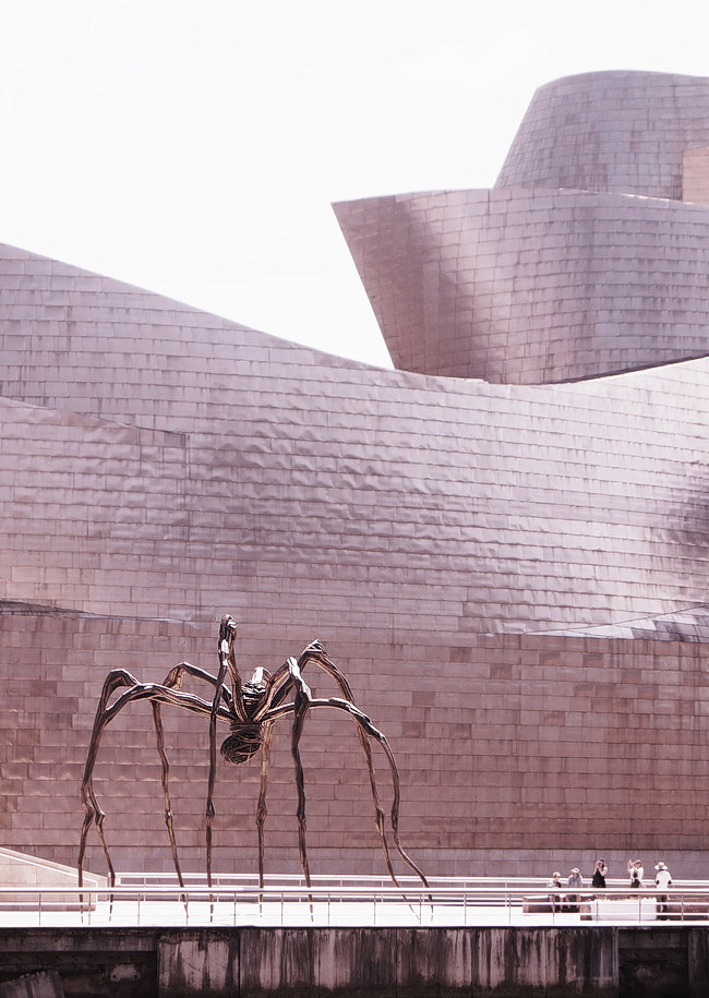 """Maman, a giant spider on its slender, knobbly legs by the artist Louise Bourgeois. """"The spider – why the spider? Because my best friend was my mother and she was deliberate, clever, patient, soothing, reasonable, dainty, subtle, indispensable, neat, and as useful as a spider… I shall never tire of representing her. I shall never tire of representing her."""""""