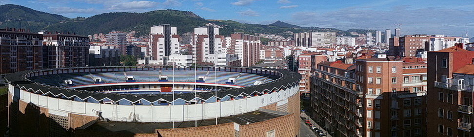 From the balcony: the bullring – a bullfighting arena or plaza de toros, rebuilt after a devastating fire a few decades ago. From above this might seem like a big open eye built between the city's lush green slopes.