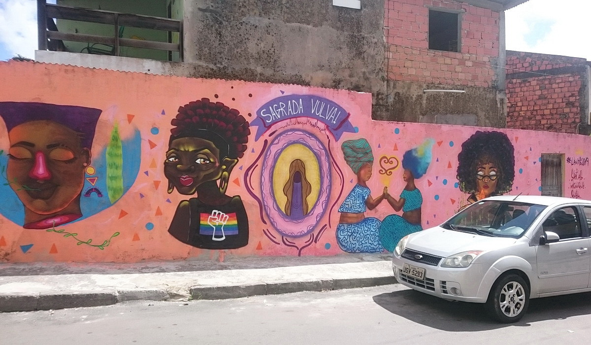 This is an average neighbourhood where active street life and colourful murals are in contrast with the rather monotonous rows of houses.